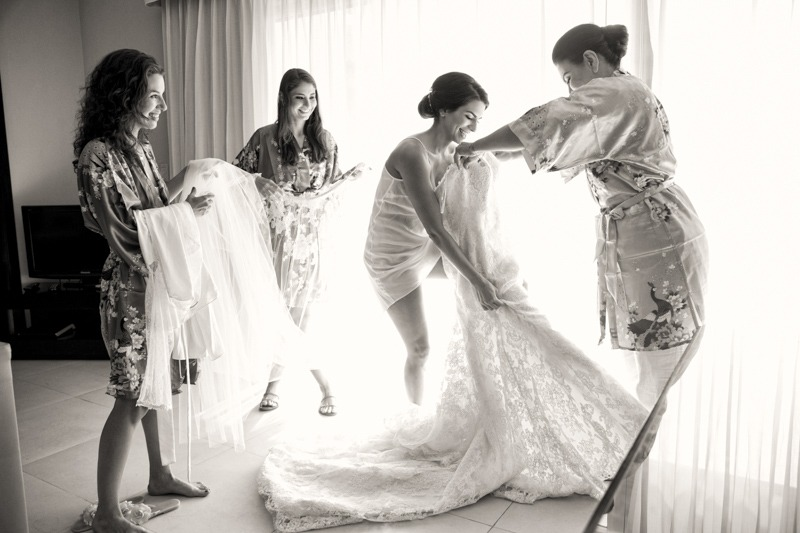 A (203) Bride getting into wedding gown with mom and bridesmaids- Azul Fives Mexico wedding photographers