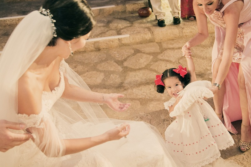 A (218) Flower girl carrying rings in Xcaret church- Mexican wedding photographers