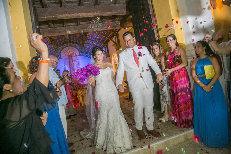 A (221)-Bride and groom walking down the aisle while guests throw petals at them - wedding photographers in Mexico