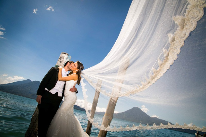 Bride and groom at Panajachel piers with volcanoes in Lake Atitlan- Hotel Atitlan wedding photographers