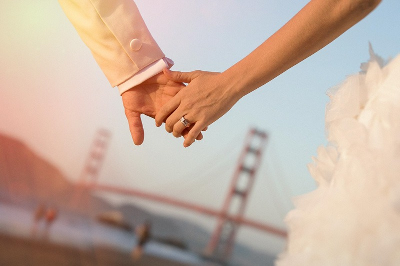 Bride and groom holding hands and Golden Gate Bridge- San Francisco wedding photographers