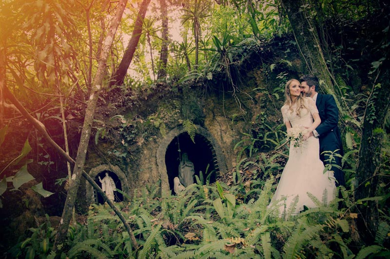 Bride and groom in forest with religious statues-wedding photographers in Guatemala