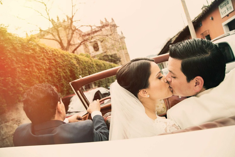 Bride and groom kissing in classic car- Weddings in Antigua Guatemala