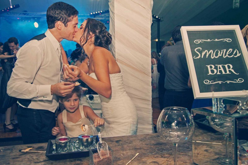 Bride and groom kissing with flower girl eating smores in San Bernardo - Guatemala wedding photos