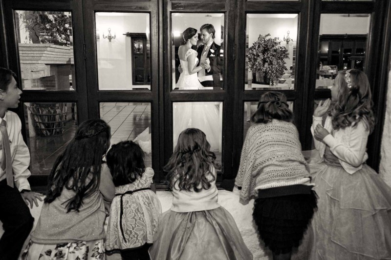 Bride and groom practicing first dance with kids peeking- Hacienda Nueva Guatemala wedding photographer