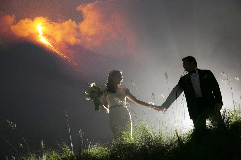 Bride and groom with Fire volcano in eruption in Antigua Guatemala- La Reunión Golf Resort Wedding photographers