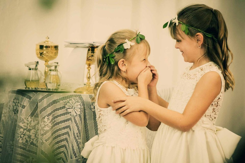 Flower girls giggling in church- destination wedding photographers Antigua Guatemala