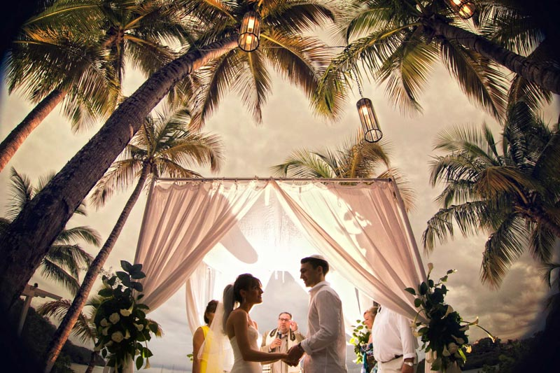 Jewish beach wedding ceremony under palm trees at sunset in Carlisle Bay Hotel- Antigua and Barbuda wedding photographers
