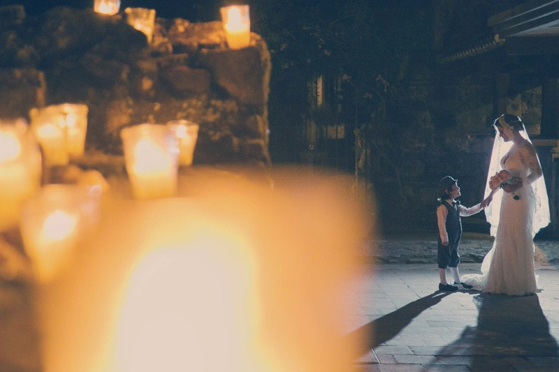 Night photo of bride and ring bearer with candles- Casa Santo Domingo wedding photographers