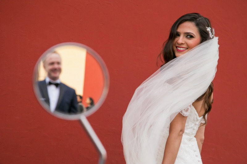 TC-1093 Bride with groom reflected in a byke mirror and a red wall in the streets of Antigua Guatemala - Colonial town wedding photographers