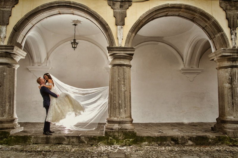 TC-1103 Groom lifting bride in a colonial building with a cobblestone street - Antigua central park wedding photos