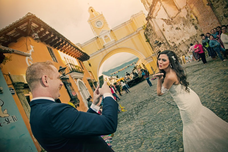 TC-1166 Groom taking photos of the bride with the Santa Catalina arch- Antigua guatemala Wedding photographers