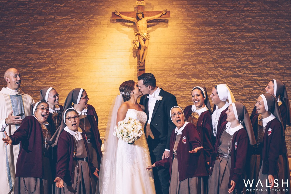 nuns and father looking at bride and groom kiss
