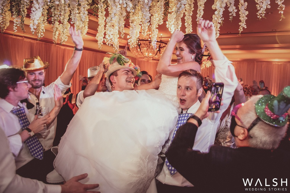 bride carried by guests at wedding